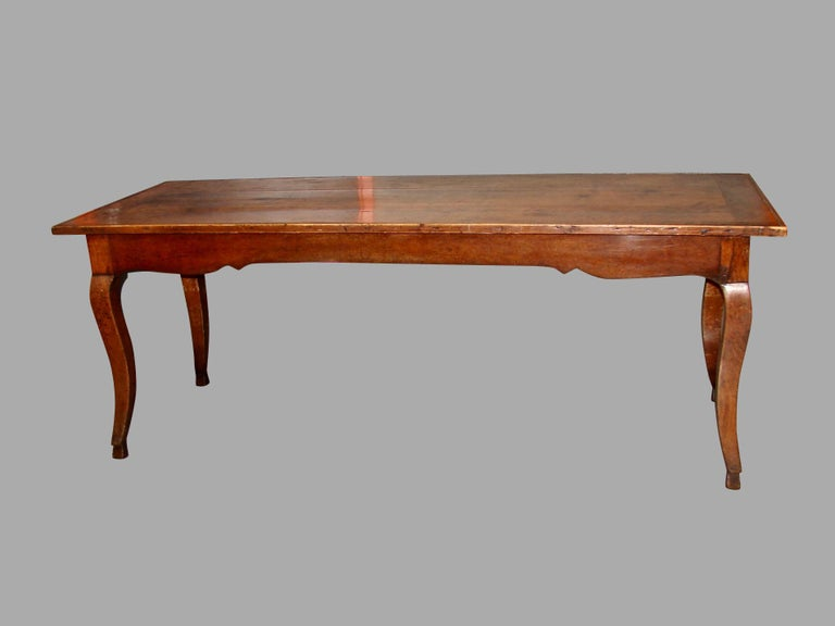 A good French fruitwood farm table with a breadboard top and scalloped apron resting on cabriole legs ending in hoof feet. The piece has peg construction throughout, with a single long cutlery drawer at one end. Lovely old color and patina, circa