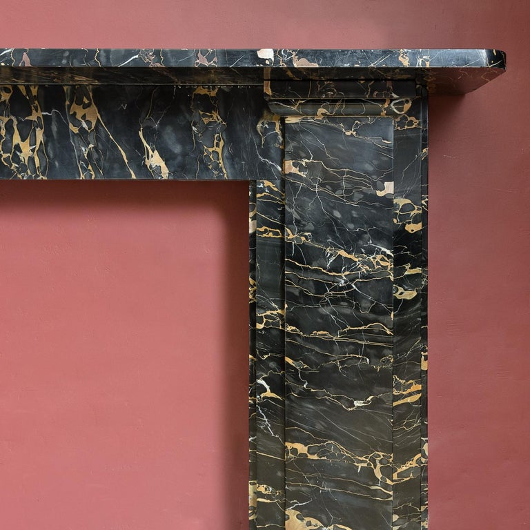 An English 19th century Portoro marble chimneypiece, circa 1830, of understated architectural design, the rectangular shelf supported on plain pilaster jambs.