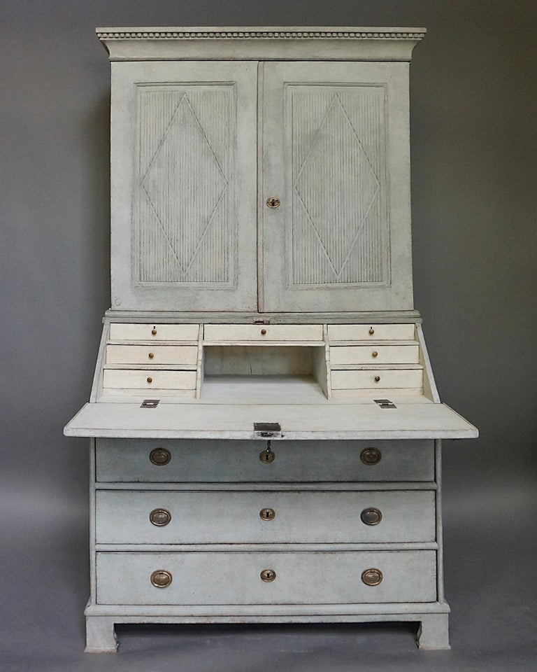 Period neoclassical secretary in two parts, Sweden circa 1840. The upper section has a straight cornice with dentil molding and double doors with raised, reeded panels with incised lozenges. Inside are three shelves with a central divider. The lower