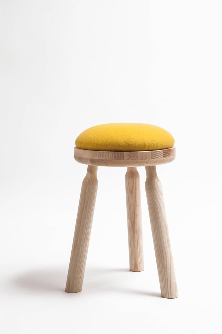 The Ninna stool structure is entirely crafted from hand-turned ashwood materials. The assembly points are tapered to form a sleek bottleneck shape similar to the design of the Ninna armchair.