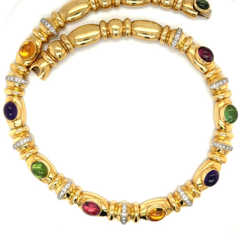 Designed by Nino Verita of Italy , this 18 karat yellow gold necklace is a true classic. The necklace is set with 8 bezel set cabochon semi precious stones of citrine, amethyst, pink & green tourmaline. Eight white gold diamond 0.90 carat rondelles