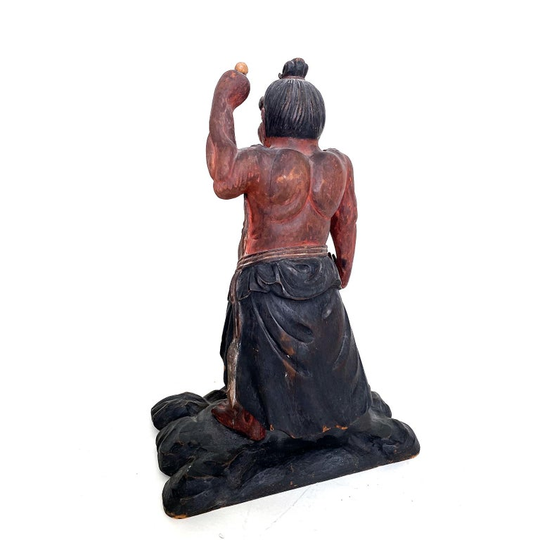 Nio, Guardian of the Buddha Guatama, polychrome wood, Japanese, Late Meiji  One of the two ferocious and muscular guardians of the Buddha Guatama. Standing on a wooden platform, one arm raised holding a skull, distended stomach, rippling muscles,