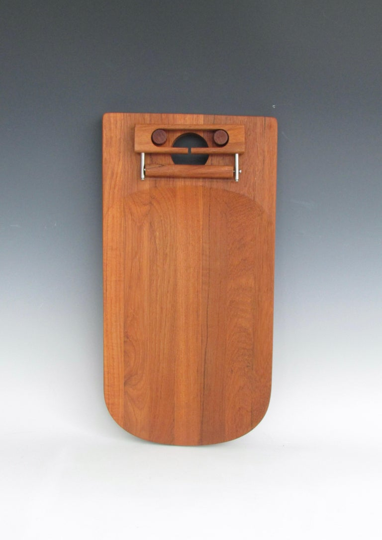 As new never used Danish teak wall hung chheeseboard. Cleverly mounted cheese cutter with board stamped Nissan.