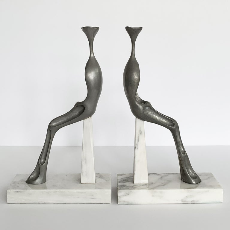 Cast aluminum sculptures on white Carrara marble bases by Peoria, IL artist Nita K Sunderland, circa 1970s. The abstract sculpture of a seated woman features a truncated stylized head. Signed NKS and numbered by the artist (numbers 1 and 3 in an