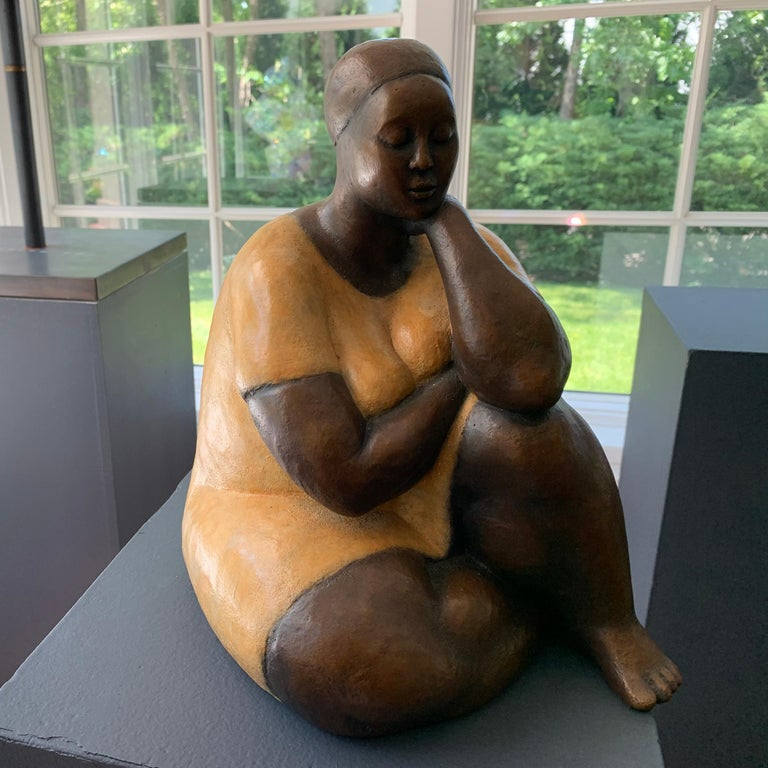 Nnamdi Okowkwo's stylized seated woman in an attitude of tranquility. To create it, he first sculpts the figure in clay, then casts it in bronze using the lost wax technique. A hot patina is applied using compounds that are specifically formulated