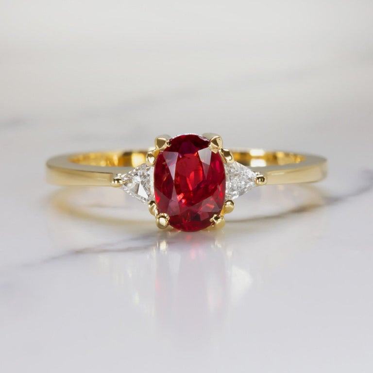 An exquisite rich color and bright sparkle, this elegant ring pairs a 0.82 carat unheated ruby with a pair of vibrant trillion cut diamonds. The 0.82 carat ruby is certified as unheated, and it is an absolutely stunning, even, and richly saturated