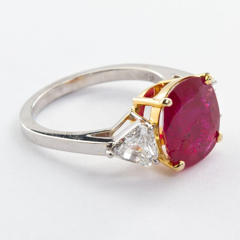 A 4.23 carat no-heat Cushion Burmese ruby as stated in the accompanying GIA Ruby Origin Report, set in a platinum and 18k gold ring with two kite shaped diamond side stones (1.50 ctw).  See GIA Report image.  No. TMWJ-7832