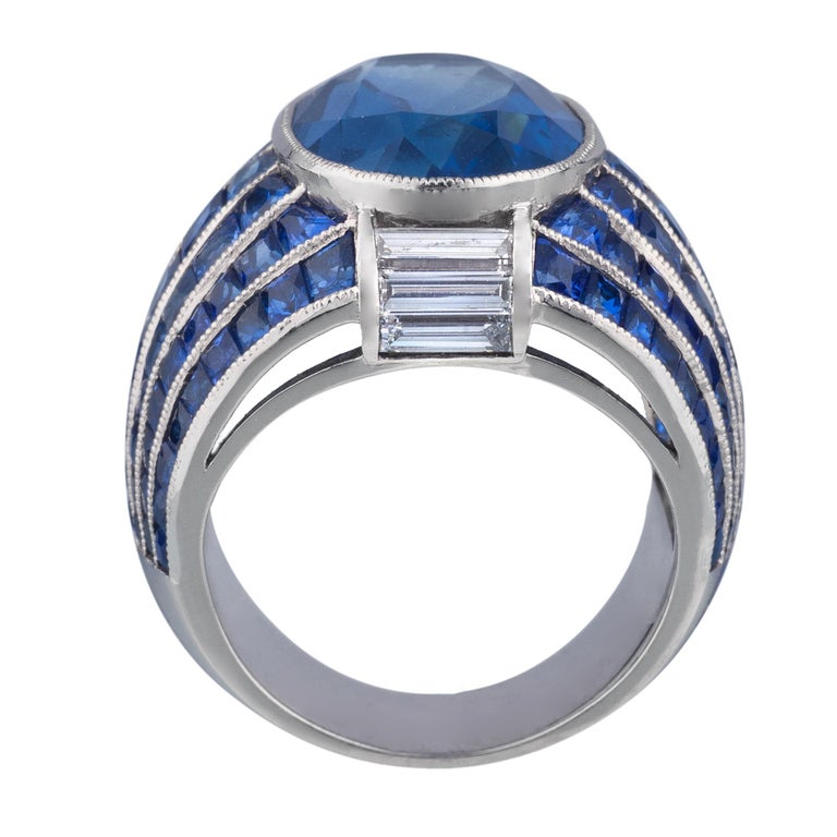 Platinum Ring with 13.53 carat Burma Sapphire and smaller sapphires weighing 7.48 carats and diamonds weighing 0.69 carats.
