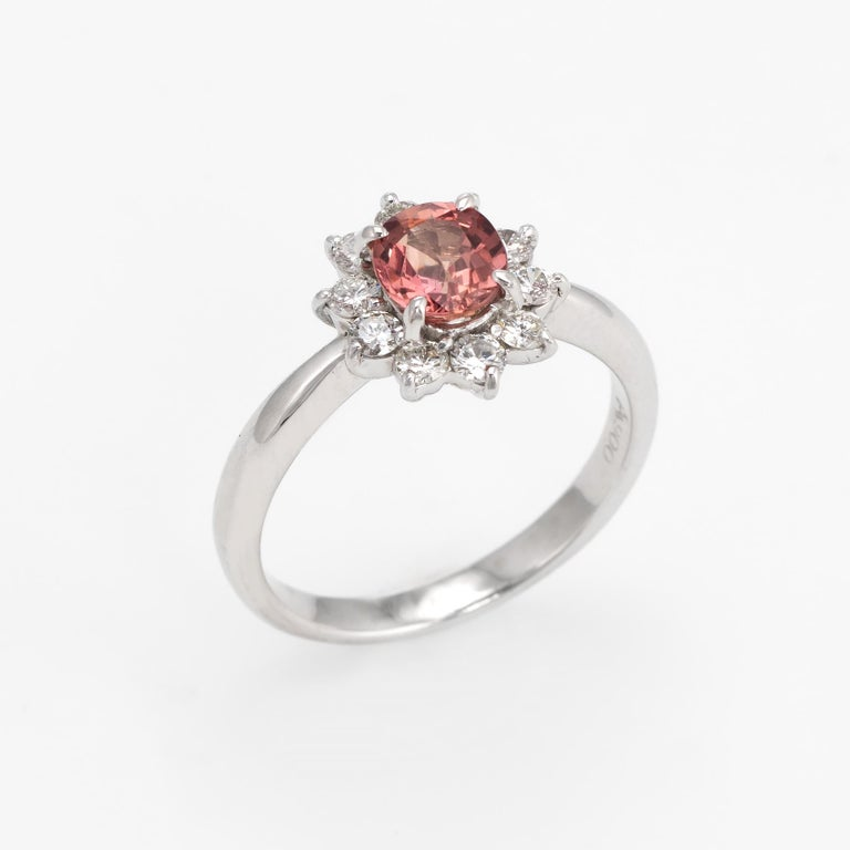 Elegant & finely detailed natural Padparadscha pink sapphire & diamond ring, crafted in 900 platinum.   One oval shape mixed cut natural Padparadscha sapphire, 0.77 carats (5.95 x 5.00 x 3.05 mm), medium pinkish-brownish orange color, lightly