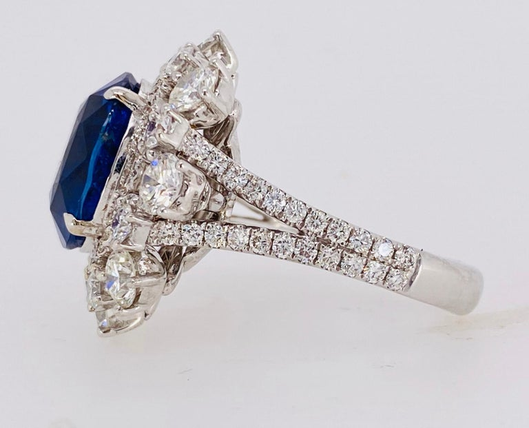 A single, unheated, oval Blue Sapphire with Round Brilliant cut Diamonds are set in a hand fabricated, 18k white gold setting.  Certified Sapphire:  8.82 carats 16 Round Brilliant Diamonds plus Diamond pave:  3.86 carats total  Size 6 1/2 1st