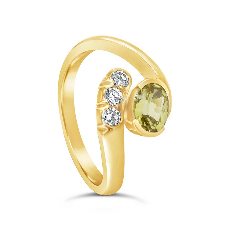 Showcasing a gorgeous 0.95 carat oval cut no heat yellow sapphire, accented with three round brilliant diamonds. Set in a bypass setting made in 18 karat yellow gold.   Style available in different price ranges. Prices are based on your selection of