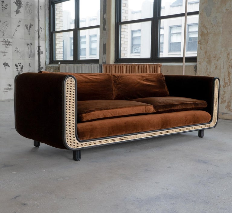 The Nº105 couch is composed of a natural cane sofa back, seat back and face which allows air and pass through the seat back and arms. Steam-bent ebonized ash trim wraps the front and back profile. Cushions are made from foam and down fill. Sofa