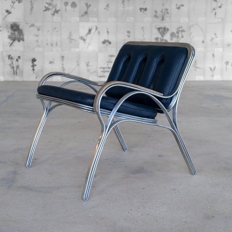 The Nº117 lounge seat is composed of individual bands of aluminum that diverge into singular entities and converge into a triplicating motif as they fluidly form the shape of the frame. Wood steam-bent arms and blue leather with triplicating