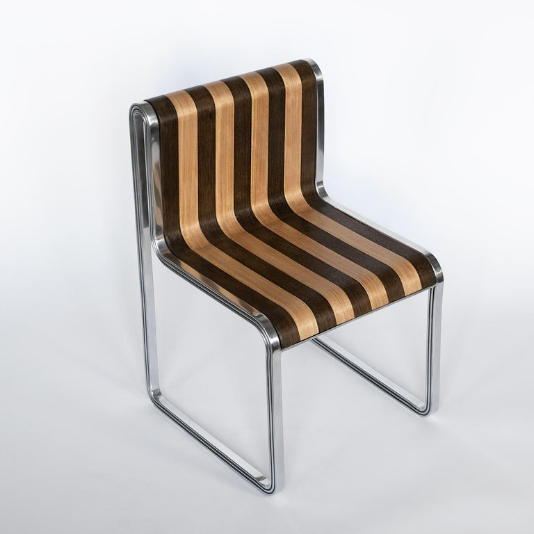 The Nº135 supper chair is composed of two polished aluminum side frames and a seat finished in ebonized/natural vertically-striped veneer. Collection Nº1 / Tripartite from Avoirdupois is the visual division of three. Every piece shares commonality