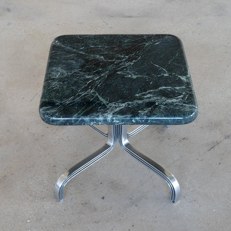 The Nº189 side table is comprised of four metal legs bending sharply into one another to create a vertical repeating motif leading to a cushion-shaped green marble top surface. Collection Nº1 / Tripartite from Avoirdupois is the visual division of