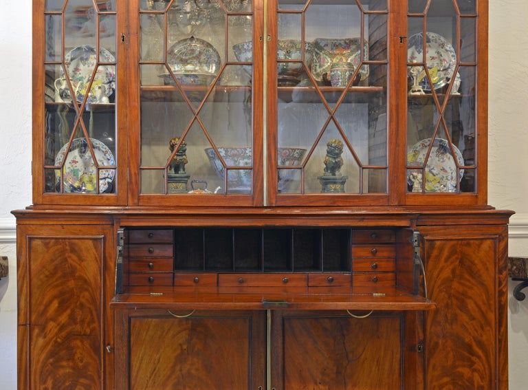 This stately secretary bookcase of great proportions features a central drawer which upon pull out opens up to an interior fitted with smaller drawers and open compartments above a mahogany writing surface. The four glazed doors of the upper section