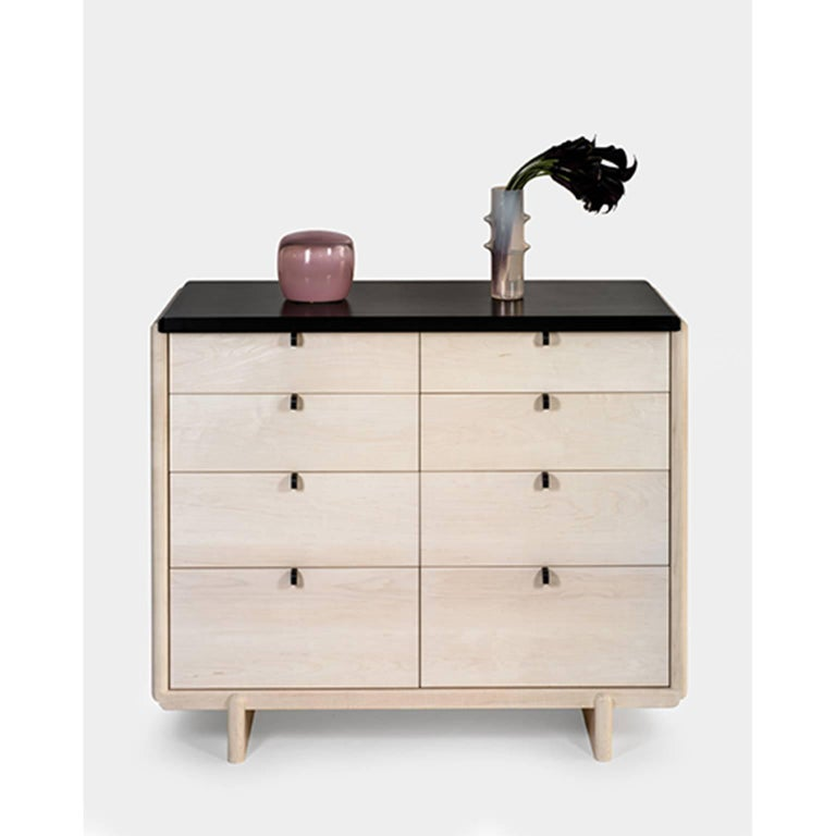Nocturne Chest softens the acute rectilinear details of traditional case construction with a composed series of undulations in the joinery. These bleached maple elements are punctuated by the bold, matte, black solid surface top and pulls. The