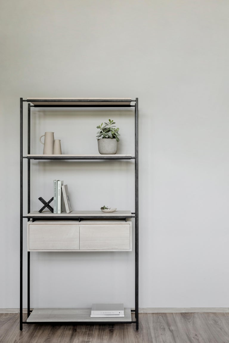 Bookcase with drawers and shelves in white oak veneer on steel structure in black color electrostatic paint.