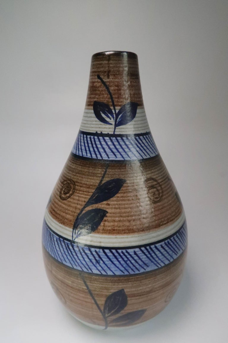 Swedish Mid-Century Modern hand painted vase by Rörstrand in the 1960s. Organic colors and decorations. Cedar and light oak brown, grey stripes, light and navy blue stripes, and dark blue vines with leaves from base to top. Stamped and signed under