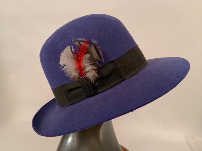 A classic Stetson hat in an striking shade of blue wool is accented with a black grosgrain ribbon hat band with multi color feather trim. The crown can be worn as photographed or pinched at the center front for that classic