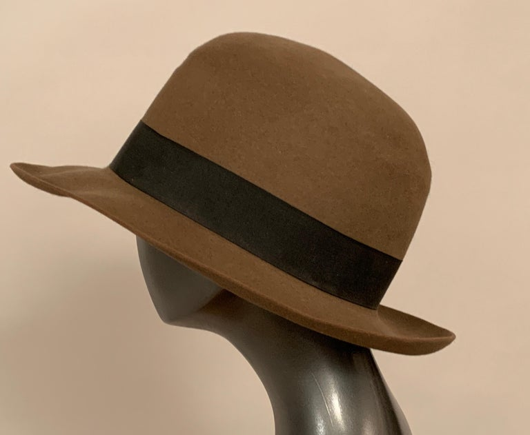 A classic taupe wool Stetson hat is accented with a deep brown grosgrain ribbon hat band. The crown can be worn as photographed or pinched at the center front for that classic