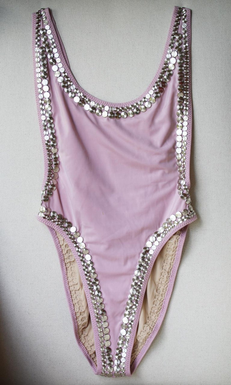 Designed with the signature high-cut legs and a deep scoop back, this 'Marissa' version is embellished with polished mirror-like studs along the edges.  Pink stretch-nylon.  Pulls on.  82% Nylon, 18% spandex; lining: 100% nylon.   Size: Large (UK