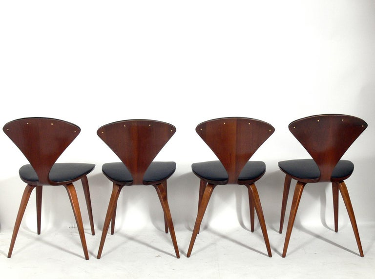 Set of eight sculptural dining chairs, designed by Norman Cherner for Plycraft, American, circa 1950s. They have all been refinished and reupholstered in black vinyl. They measure: 31.25