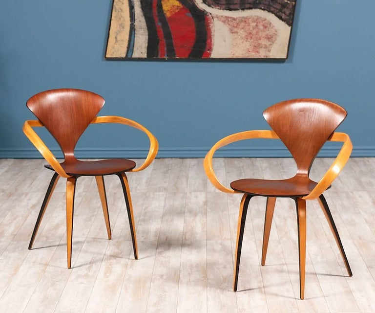 Price Each  Pretzel Arm Chairs designed by Norman Cherner for Plycraft Co. c. 1950's. Originally designed to make Mid Century Modern design accessible to the masses, this incredible design features walnut-faced molded plywood and laminated birch