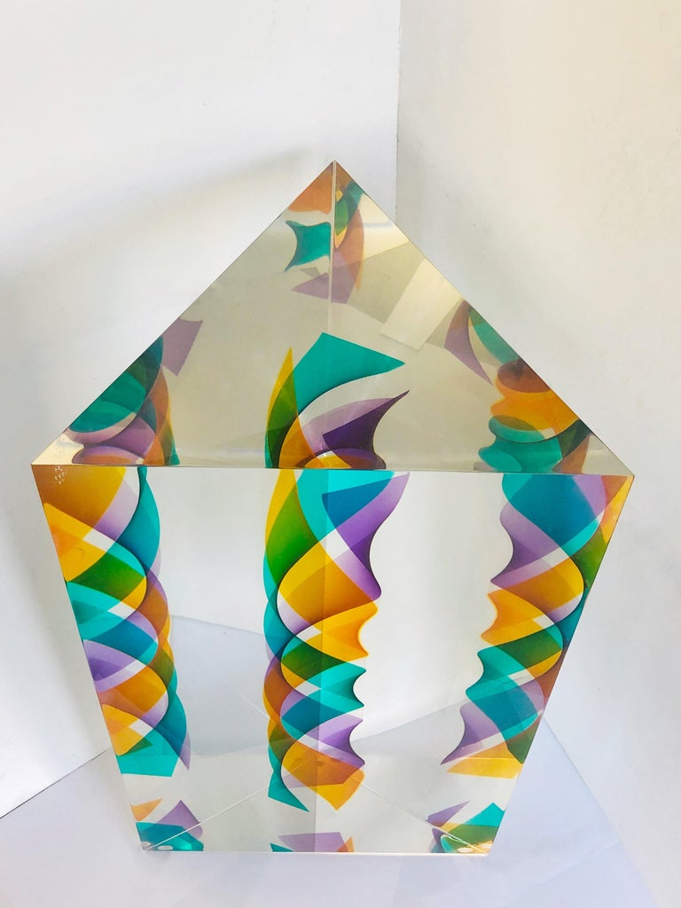 A monumental Lucite sculpture by Norman Mercer. A solid Op Art monolithic triangular sculpture. There is a colorful spiral at the center that appears to multiply when seen from different angles. Each side is 16.5