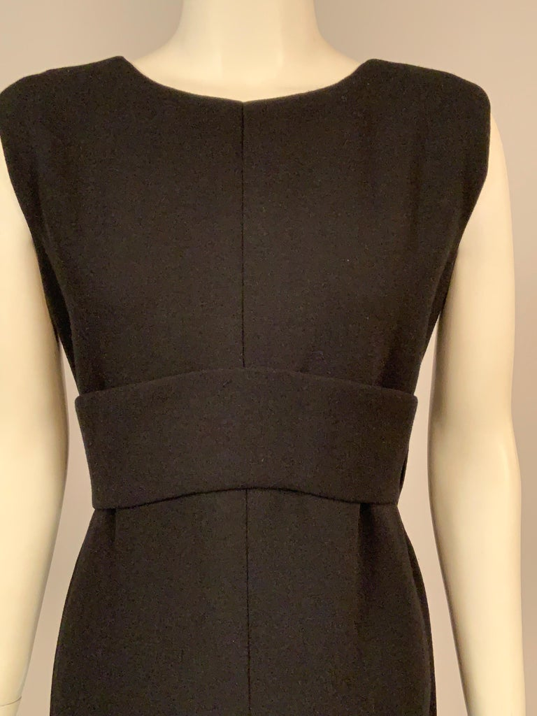 This classic black wool crepe evening dress from Norman Norell is as stylish today as it was in the 1960's, and it is a perfect backdrop for your favorite jewelry. The sleeveless dress has a round neckline and an Empire waist created by a wide black