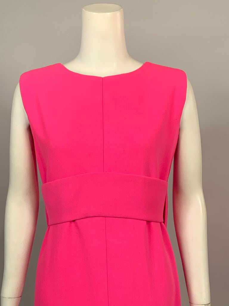 This classic bright pink wool crepe evening dress from Norman Norell is as stylish today as it was in the 1960's, and it is a perfect backdrop for your favorite jewelry. The sleeveless dress has a round neckline and an Empire waist created by a wide