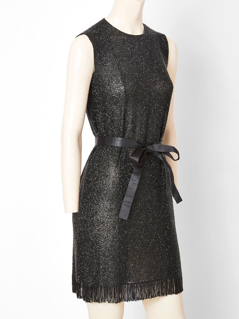 Norman Norell, sleeveless, black, bugle beaded sheath having a satin belt that ties at the waist and a beaded fringe embellishing the hem.