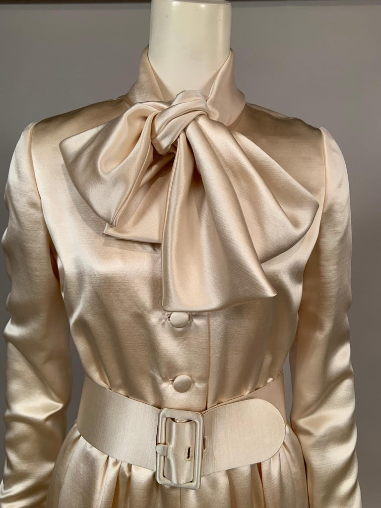 Dress, coat or coat dress, you decide or wear this piece three different ways. The cream silk satin dress, designed by Norman Norell for I. Magnin still has the original 1960's price tag of $2395.00. It also has the envelope of extra buttons and the