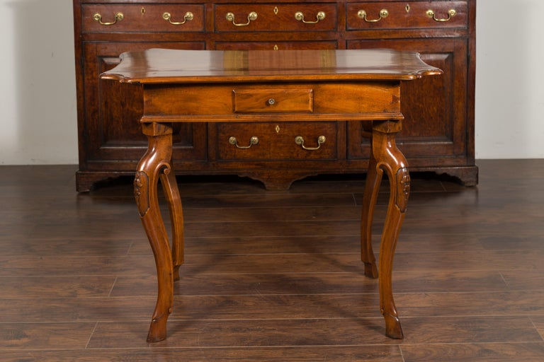 A Northern Italian Régence period walnut side table from the early 18th century, with four drawers, cabriole legs, hoofed feet and carved foliage. Created in Northern Italy during the first quarter of the 18th century, this walnut side table