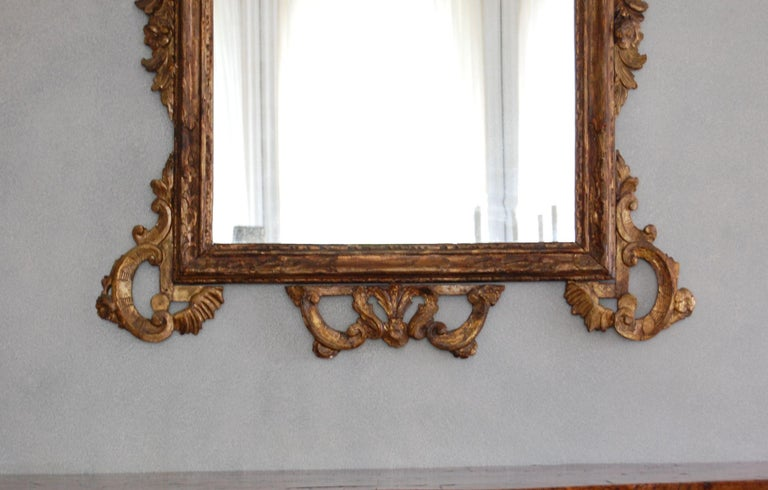 A northern Italian giltwood mirror surmounted by a further flower decorated plate and floral clasp, surrounded by C- scroll and foliate borders. Center glass is a 19th century replacement. Very good overall condition.