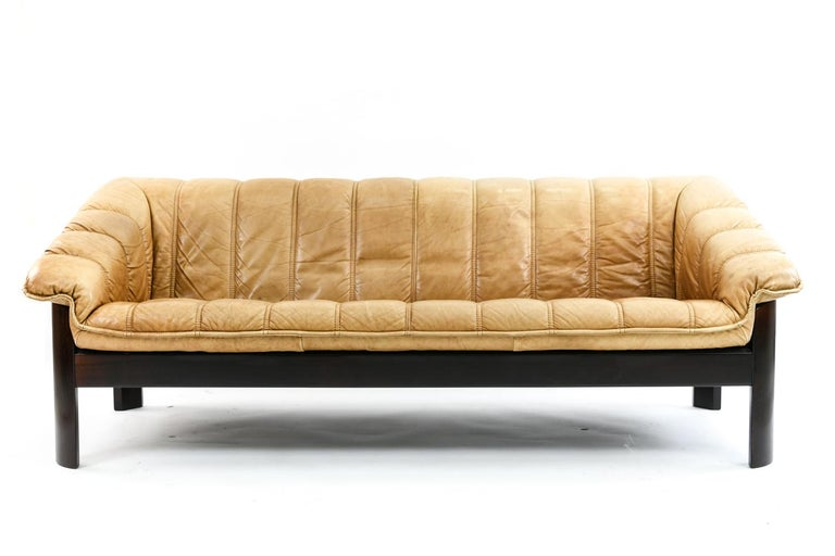 A beautiful leather sofa by Norwegian design company Ekornes in the style of Jean Gillon on a stained beech wood base. The patina on this rich brandy color leather is beautiful, comfortable and of high quality. Perfect for a city loft or midcentury