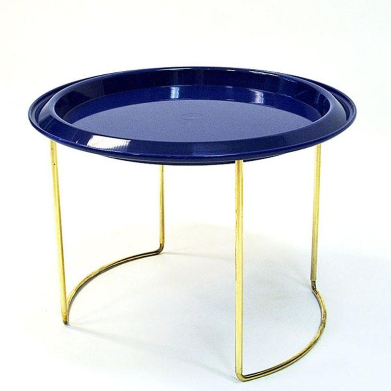 Beautiful Norwegian round tray table on a foldable brass foot designed by Herman Bongard for PLUS Norway in the 1960s. This practical little table has two removable plastic table tops. One bright blue and one light transparent grey plate. You can
