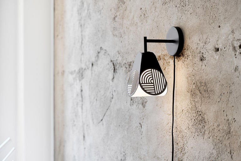Notic sconce lamp by Bower Studio Dimensions: 18 x 15.5 cm (Ø)   Notic is an homage to classical architectural elements. The graphical metal shade embraces the complex geometry of the glass and spreads the light in a hypnotic way. The lamps have