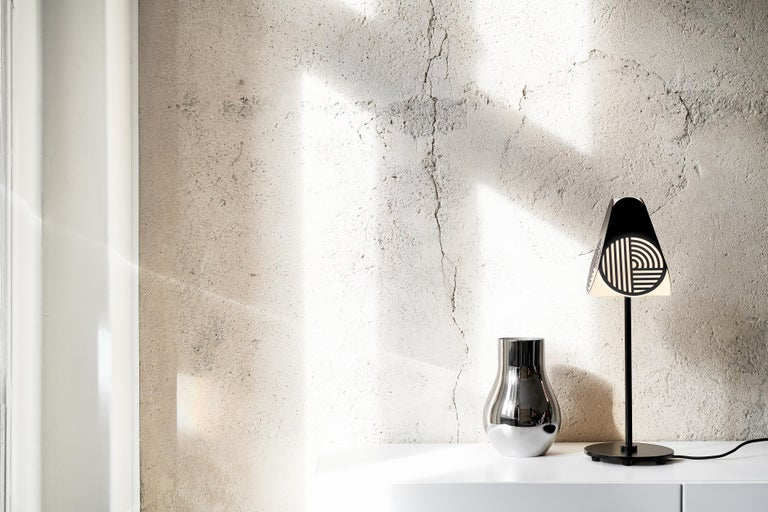 Notic table lamp by Bower Studio Dimensions: 47.5 x 15.5 cm (Ø)   Notic is an homage to classical architectural elements. The graphical metal shade embraces the complex geometry of the glass and spreads the light in a hypnotic way. The lamps
