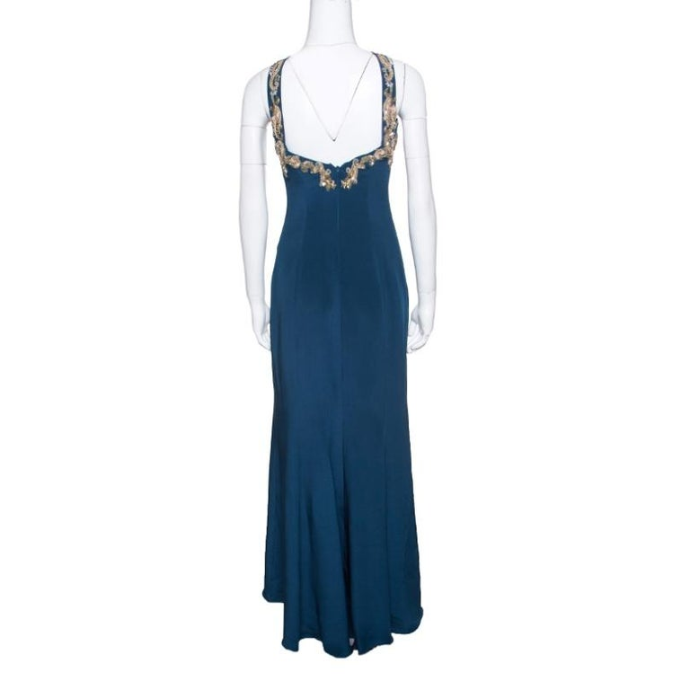 You'll find reasons to wear this stunning Notte by Marchesa dress. This peacock blue maxi dress is made of 100% silk and features a flattering silhouette. It flaunts a cross strap neckline with beautiul sequins, beads and crystals adorning the