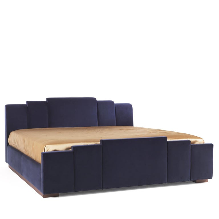 Part of a collection that takes inspiration from the creative silhouette of 1980s furniture, this stunning bed frame is marked by a geometric headboard fashioned of navy blue fabric mirrored in a smaller size on the front.