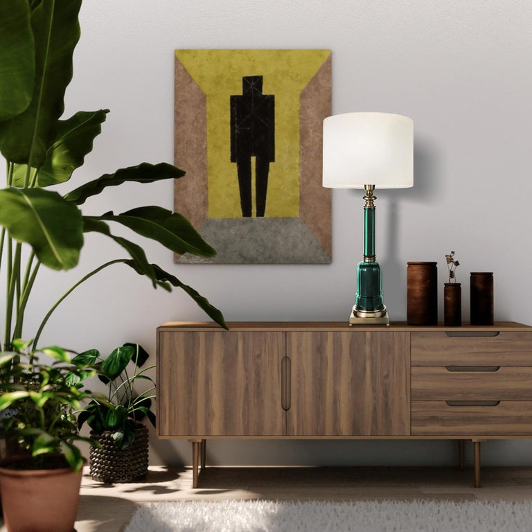 The Novecento lamp in spectacular green is a beautifully decorative item in brass and colored glass. Featuring a square pedestal with golden ball feet to support the glass body of the lamp, this fashionable accessory may carry imperfections that add