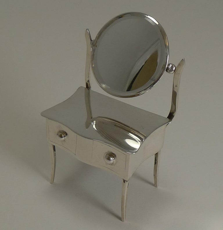 A really charming novelty sterling silver jewelry or ring box modelled in the form of a dressing table including a swing mirror to the back with it's original beveled mirror (minor surface scratches to mirror commensurate with age).  The
