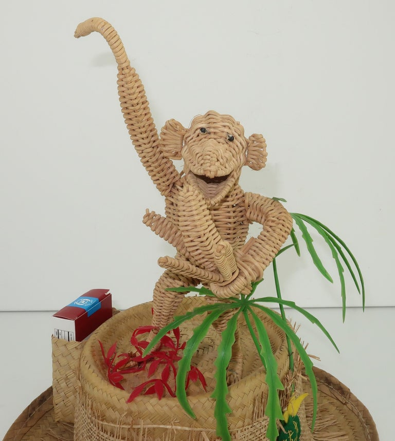 Ready to monkey around?  This C.1960 novelty straw hat is the perfect beach bum companion complete with a charming monkey snacking on bananas and a container for storing your cigarettes ... what more could you need!?  The brim is decorated with a