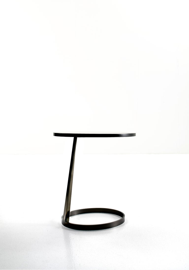 Metal base painted and finished under high heat in col. Opaque black nickel or black. Top in round or oval shape can be in painted glass or in mat or polished lacquered wood.  Marco Corti was born in Milano in 1960. He Graduated at Politecnico of