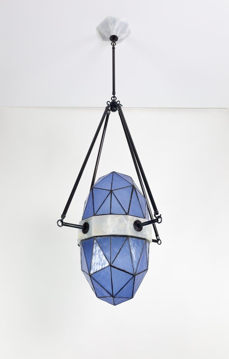 """Nucleus is a large-scale pendant in Onyx and glass made to order by Kalin Asenov studio.   Dimensions: L: 30"""" H: Variable"""" W: 18""""  Materials: glass Onyx Patinated brass, Patina  The listing is for Sapphire finish and Aged brass with patina."""