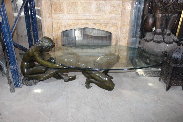Classical Renaissance pair of sculptures encompassing beauty and tension. Glass ellipse tabletop measures 86 x 175 cm.