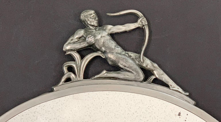 This gorgeous circular mirror surmounted by a nude male Archer figure in bas relief pewter was made in 1930s Sweden, strongly influenced by the Swedish Grace movement and the Svenskt Tenn company in particular, which commissioned Swedish artists to