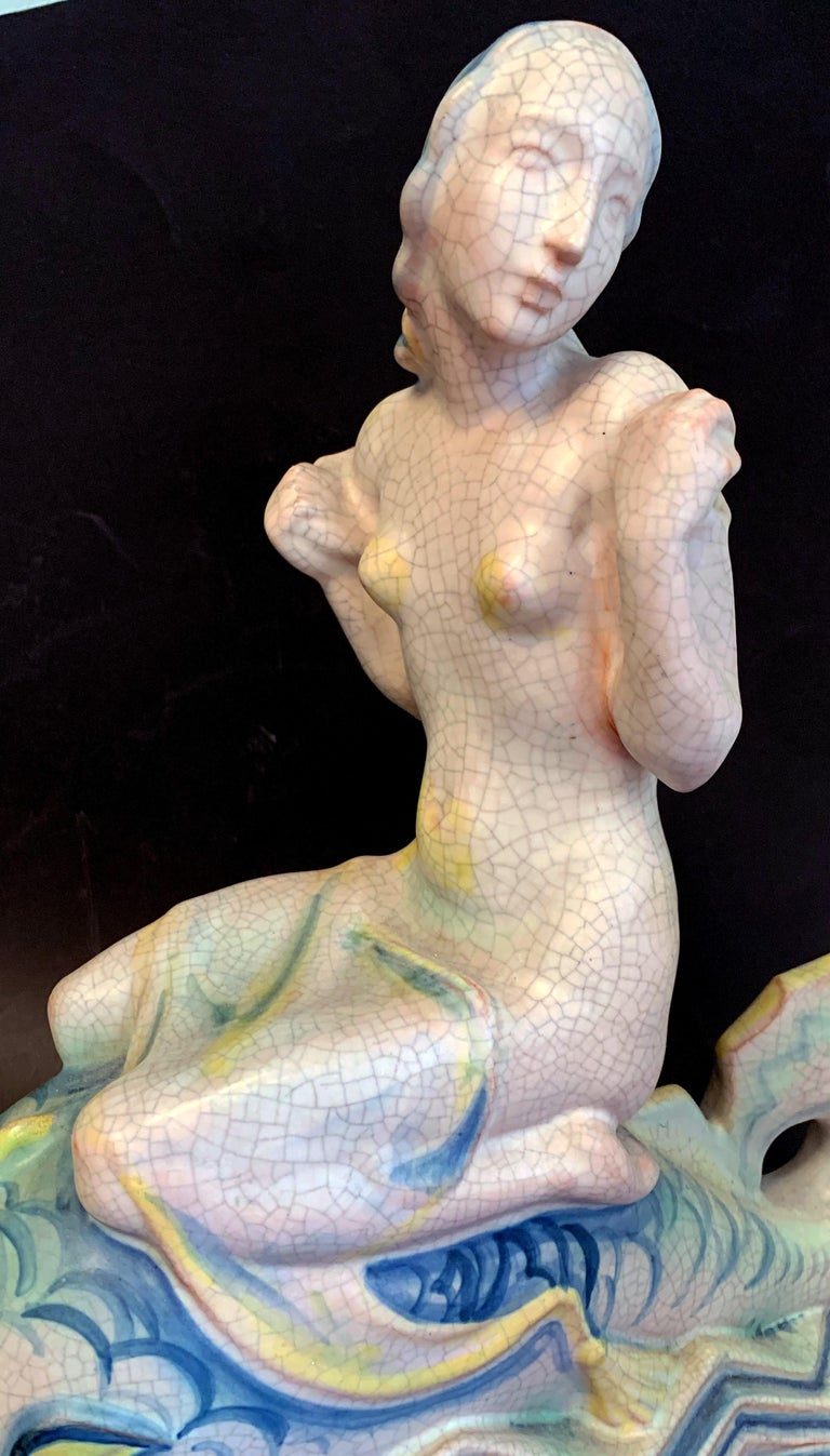 Stunning in its size, composition and rich glazes, this rare sculpture of a mermaid riding on a dolphin in an Art Deco, zigzag sea was crafted by Kieler Kunst-Keramic in Kiel, Germany in the mid-1920s. Known by Art Deco collectors for its exquisite