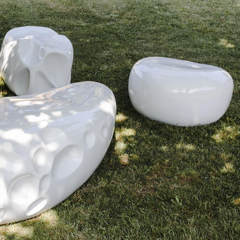 Crafted in reinforced resin to resemble an organic stone, the sculpture is suitable for both indoor and outdoor use. Shown here in white with a glossy finish, the piece can be personalized with any RAL color.